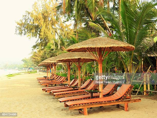 Umbrellas Over Lounge Chairs On Shore