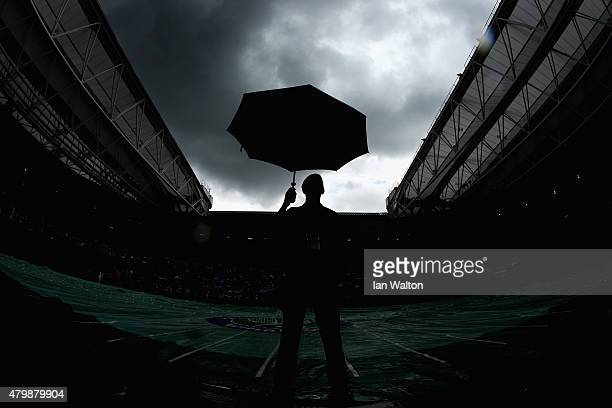 Umbrella's pop up during a rain delay on day nine of the Wimbledon Lawn Tennis Championships at the All England Lawn Tennis and Croquet Club on July...