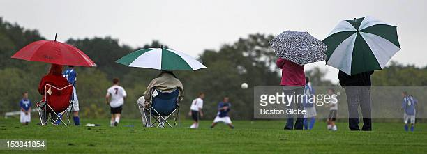 Umbrellas were the accesSory of the day as fans stay dry while the players in a boy's varsity soccer game between Beverly High School and Danvers...