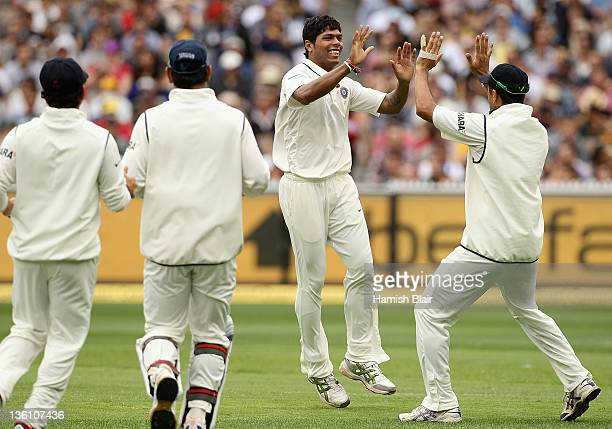Umesh Yadav of India celebrates with team mates after taking the wicket of Shaun Marsh of Australia during day one of the First Test match between...