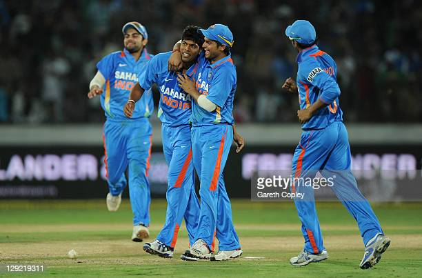 Umesh Yadav of India celebrates with teammate Suresh Raina after bowling Graeme Swann of England during the 1st One Day International between England...