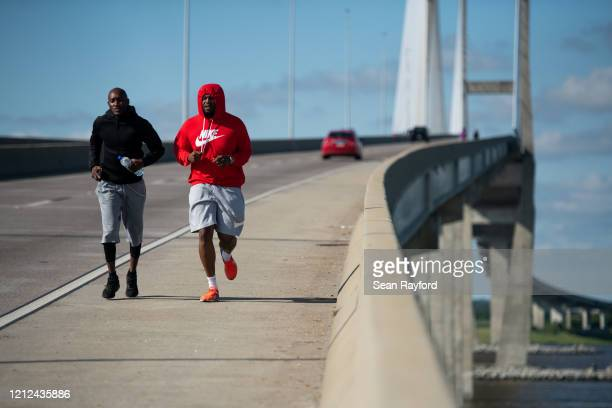 Umoja Spaulding and Ben Butler run across the Sidney Lanier Bridge to honor Ahmaud Arbery on May 9, 2020 in Brunswick, Georgia. Arbery was shot and...