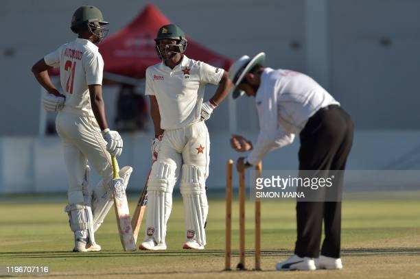 Umpire Aleem Dar puts the wickets back in the ground as Zimbabwe's Regis Chakabva and Zimbabwe's Tinotenda Mutombodzi looks on during the first day...