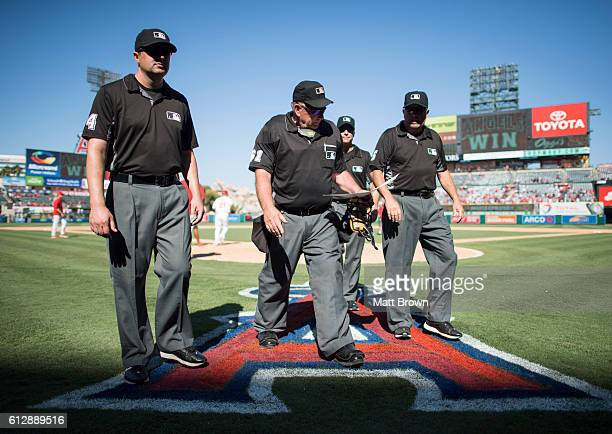 Umpire Bob Davidson centerleft #61 looks at the lineup card as he leaves the field with umpires Lance Barrett Dan Iassogna and Dale Scott at Angel...