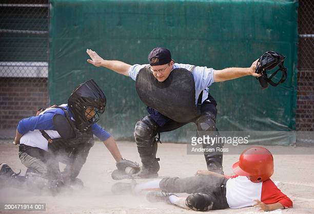 Umpire calling baseball player (8-10) safe as he slides at home plate