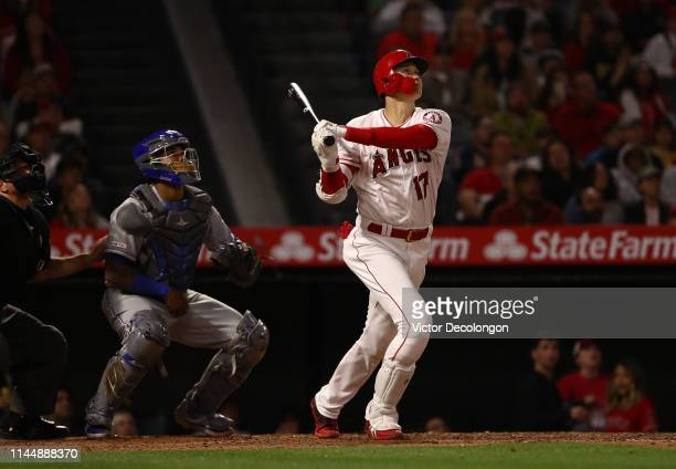 Umpire Chris Guccione catcher Martin Maldonado of the Kansas City Royals and Shohei Ohtani of the Los Angeles Angels of Anaheim watch Ohtani's hit go...