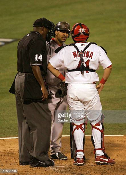 Umpire Chuck Meriwether stands between catcher Yadier Molina of the St Louis Cardinals and batter Manny Ramirez of the Boston Red Sox as they...