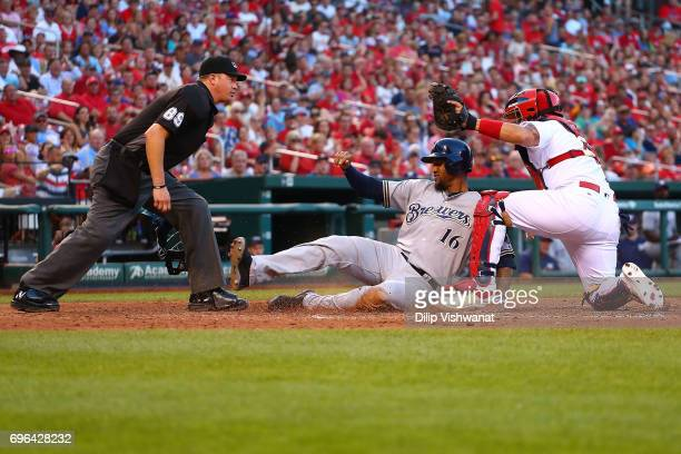 Umpire Cory Blaser watches as Yadier Molina of the St Louis Cardinals tags Domingo Santana of the Milwaukee Brewers at home plate in the fifth inning...