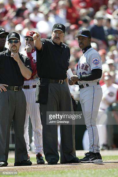 Umpire crew chief Tim McClelland points as he meets with Willie Randolph of the New York Mets and Dave Wiley of the Cincinnati Reds prior to the...