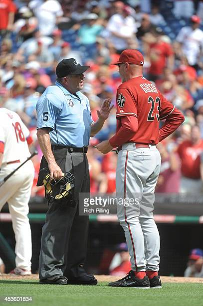 MLB umpire Dale Scott left discusses a disputed play with Kirk Gibson manager of the Arizona Diamondbacks during the game between the Philadelphia...