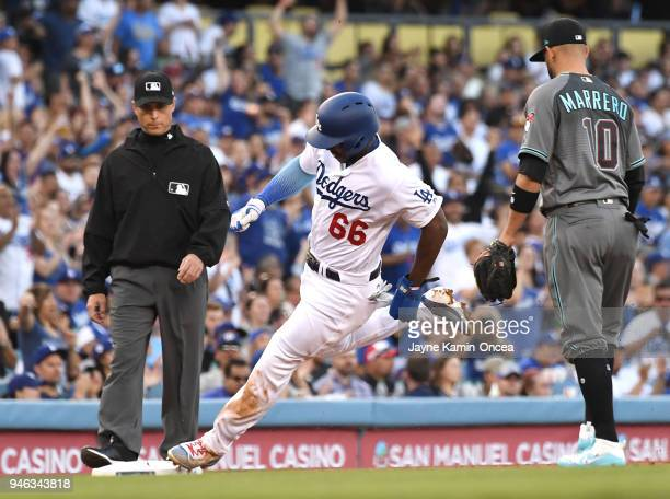 Umpire Dan Iassogna and Deven Marrero of the Arizona Diamondbacks watch as Yasiel Puig of the Los Angeles Dodgers tags third base as he heads home to...