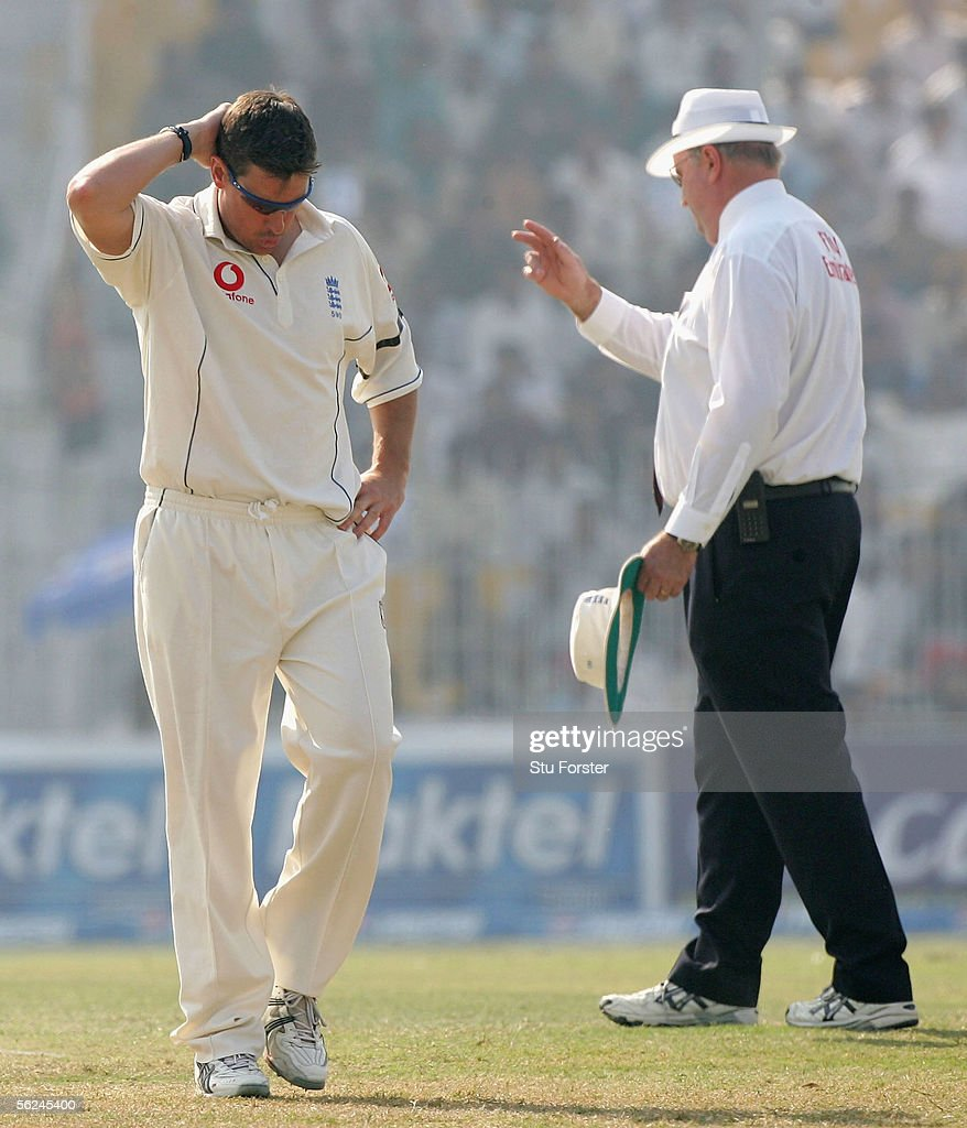 Umpire Daryll Hair signals a four while a dejected looking Ashley Giles walks away wearing a black arm band in memory of the England supporter who died of a heart attack yesterday during the Second Day of the Second Test Match between Pakistan and England at Iqbal Faisalabad Cricket Stadium on November 21, 2005 in Faisalabad, Pakistan.