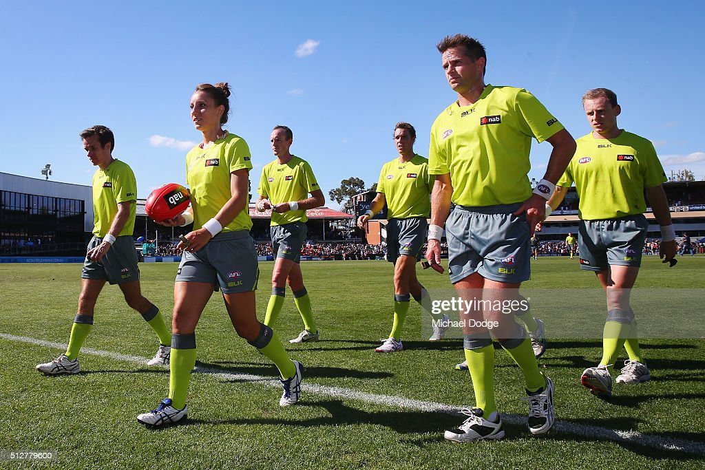 Umpire Eleni Glouftsis, becoming the first female field umpire to adjudicate an official AFL match today, leads the team off after the 2016 AFL NAB Challenge match between Carlton and Essendon at Ikon Park on February 28, 2016 in Melbourne, Australia.