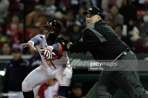 Umpire Eric Cooper pushes Outfielder Ronald Acuna Jr #13 of the Atlanta Braves to secure a clear view as Infielder Amed Rosario of the New York Mets...