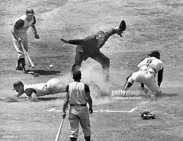 Umpire Frank Dascoli calls Bill Mazeroski of the Pittsburgh Pirates safe at the plate as the ball gets by LA Dodgers catcher John Roseboro Los...