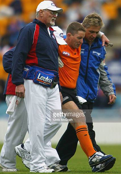 Umpire Gavin Door is taken from the field after injurying his leg during the round 6 AFL match between the Kangaroos and the Western Bulldogs played...