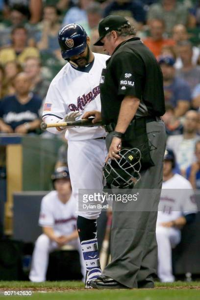 Umpire Hunter Wendelstedt inspects the bat of Jonathan Villar of the Milwaukee Brewers for pine tar in the seventh inning against the Miami Marlins...