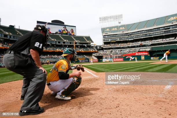 Umpire Hunter Wendelstedt stands behind Jonathan Lucroy of the Oakland Athletics as Andrew Triggs warms up during the game between the Athletics and...