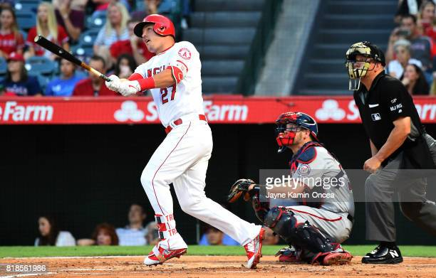 Umpire Jeff Nelson and Chris Heisey of the Washington Nationals look on as Mike Trout of the Los Angeles Angels of Anaheim hits a solo home run in...