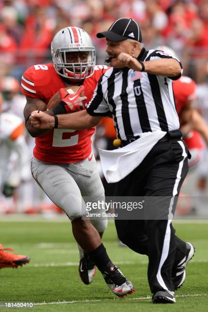Umpire Jim Krogstad attempts to get out of the way as Jordan Hall of the Ohio State Buckeyes runs for an 18yard touchdown run in the second quarter...