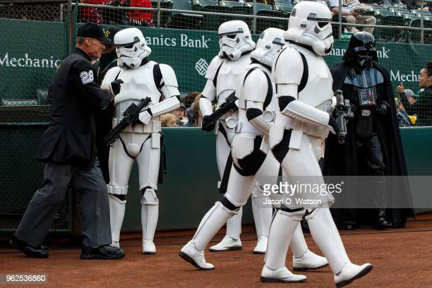 MLB umpire Jim Wolf is escorted onto the field by Star Wars Stormtroopers on Star Wars Night before the game between the Oakland Athletics and the...