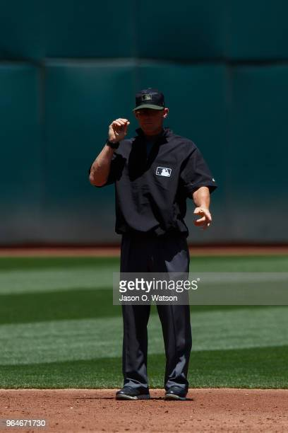 MLB umpire Jim Wolf stands on the field during the second inning between the Oakland Athletics and the Arizona Diamondbacks at the Oakland Coliseum...