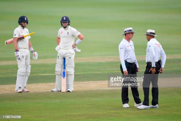 Umpire Joel Wilson and umpire Rod Tucker discuss the quality of the light and whether play should continue or not as England's Ollie Pope and...