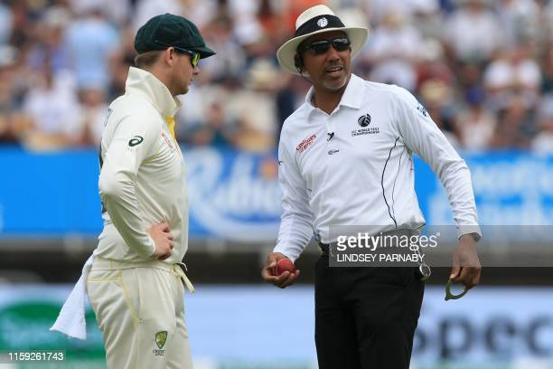Umpire Joel WIlson checks the shape of the ball as Australia's Steve Smith looks on during play on the third day of the first Ashes cricket test...