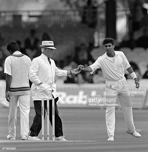 Umpire Ken Palmer ruturns the ball to Waqar Younis of Pakistan following a ball inspection during the 4th Texaco Trophy One Day International between...