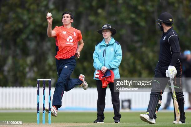 Umpire Kim Cotton looks on as Pat Brown of England bowls during the Twenty20 International match between the New Zealand XI and England at Bert...