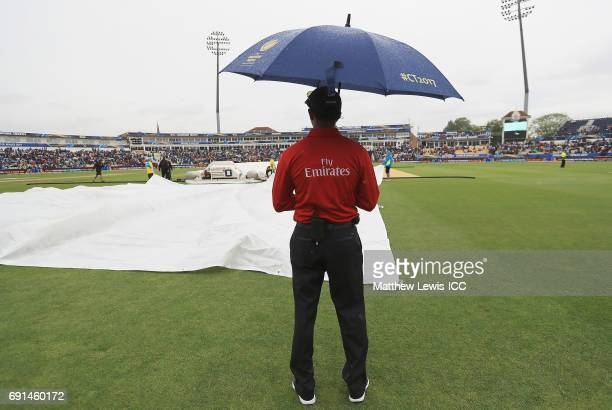 Umpire Kumar Dharmasena looks on as rain stops play during the ICC Champions Trophy match between Australia and New Zealand at Edgbaston on June 2...