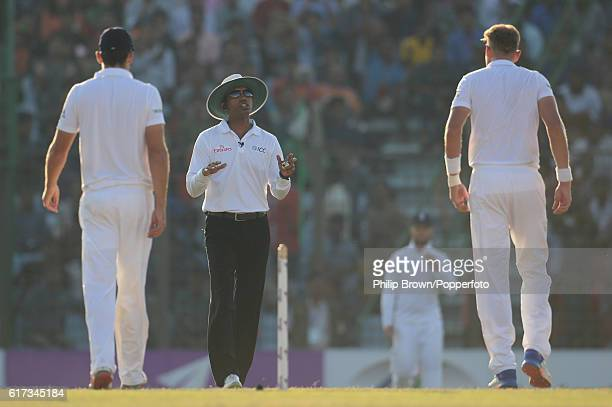 Umpire Kumar Dharmasena talks to Alastair Cook and Stuart Broad during the fourth day of the first test match between Bangladesh and England at Zohur...