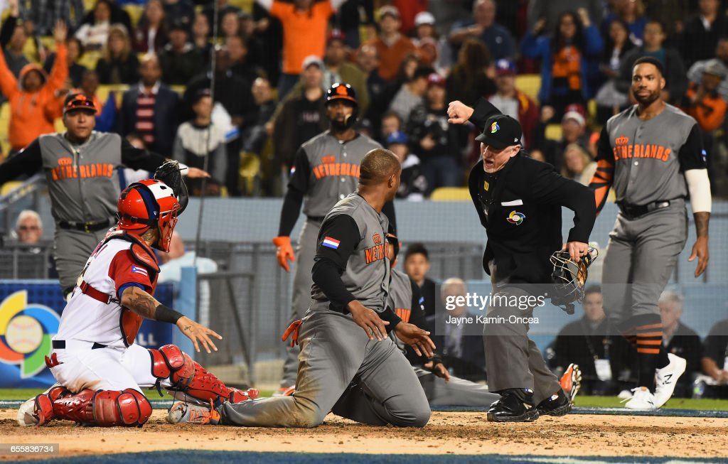 Umpire Lance Barksdale calls Jonathan Schoop #6 of the Netherlands out at home after he was tagged by catcher Yadier Molina #4 of the Puerto Rico in the fifth inning during Game 1 of the Championship Round of the 2017 World Baseball Classic at Dodger Stadium on March 20, 2017 in Los Angeles, California.