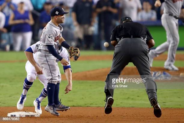 Umpire Laz Diaz is hit by a ball thrown by Chris Devenski of the Houston Astros during the tenth inning in game two of the 2017 World Series between...