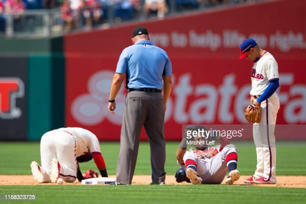 Umpire Mark Carlson and Cesar Hernandez of the Philadelphia Phillies look on after Jean Segura of the Philadelphia Phillies and Ronald Acuna Jr. #13...