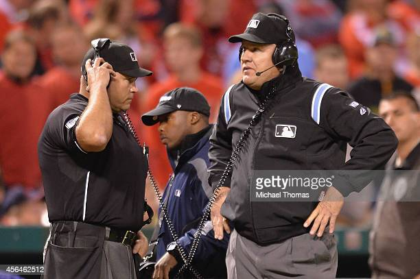 Umpire Mark Carlson consults with other personnel as they review a play using Instant Replay during a game between the St Louis Cardinals and the...