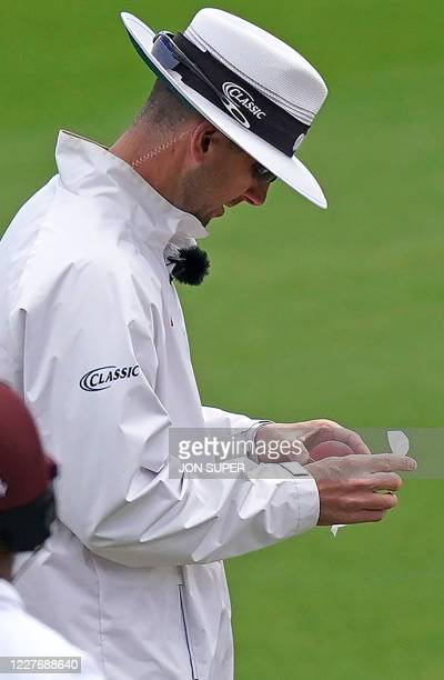 Umpire Micheal Gough uses a wipe to disinfect a bowler's saliva from the ball on the fourth day of the second Test cricket match between England and...