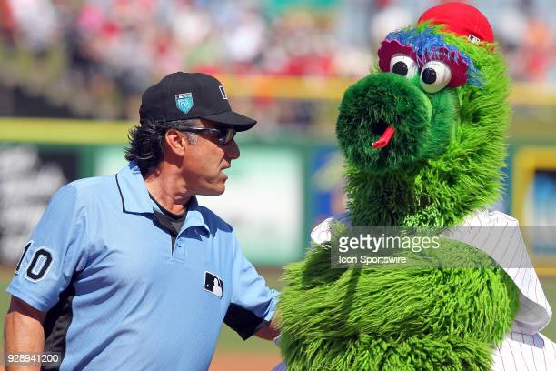 MLB umpire Phil Cuzzi has a word with the Philly Phanatic at home plate before the spring training game between the Boston Red Sox and the...
