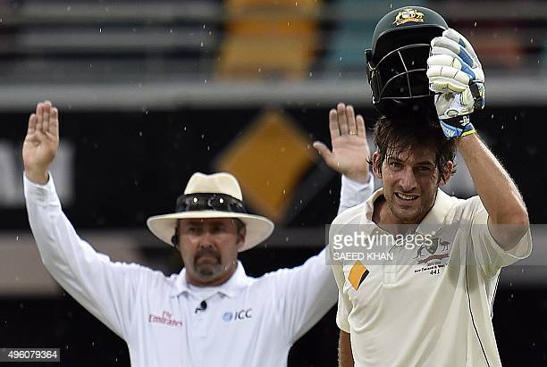 Umpire Richard Illingworth gives a sixruns signal as Australia's batsman Joe Burns remove helmet to celebrate his carrier first test century during...