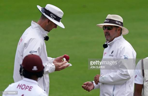Umpire Richard Kettleborough watches as Umpire Micheal Gough uses a wipe to disinfect a bowler's saliva from the ball on the fourth day of the second...