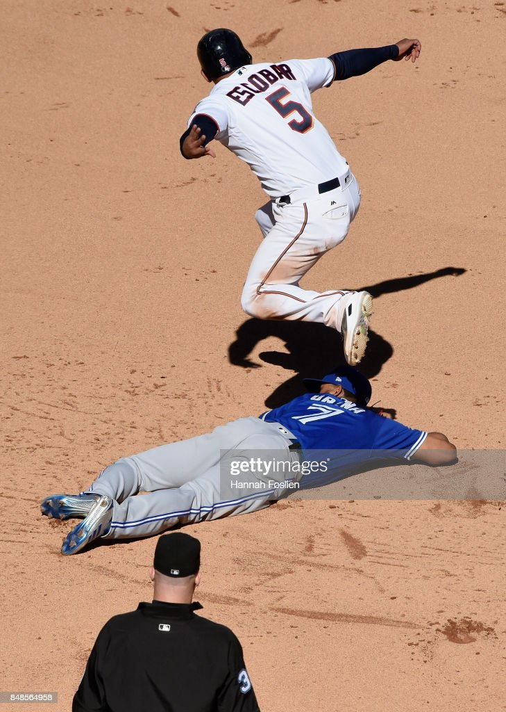 Umpire Ryan Blakney #36 looks on as Eduardo Escobar #5 of the Minnesota Twins jumps over Richard Urena #7 of the Toronto Blue Jays on his way to third base after stealing second base and the ball getting past Urena during the fifth inning of the game on September 17, 2017 at Target Field in Minneapolis, Minnesota. The Twins defeated the Blue Jays 13-7.