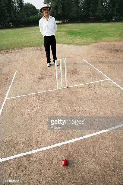 Umpire standing on the pitch behind wickets