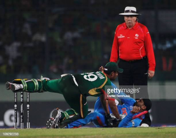 Umpire Steve Davies of Australia looks on as Tamim Iqbal of Bangladesh collides with Harbhajan Singh of India during the opening game of the ICC...
