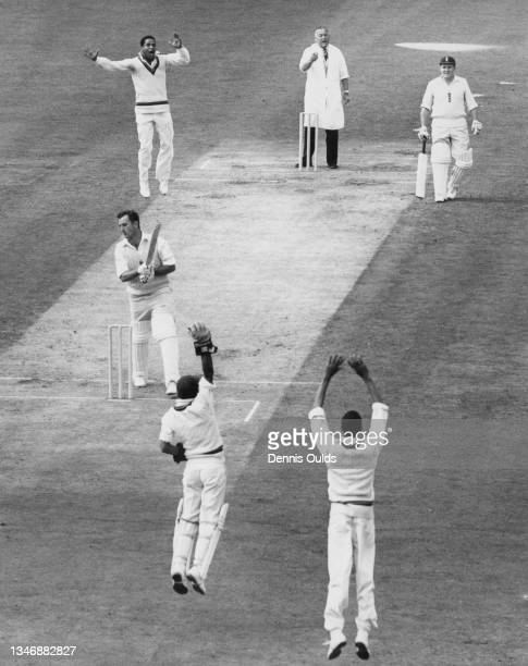 Umpire Sydney Buller points the finger at Ted Dexter of England after being caught for 27 by wicketkeeper Deryck Murray of the West Indies off the...