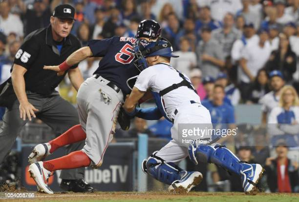 Umpire Ted Barrett looks on as Ian Kinsler of the Boston Red Sox is tagged out at home plate by Austin Barnes of the Los Angeles Dodgers on a throw...