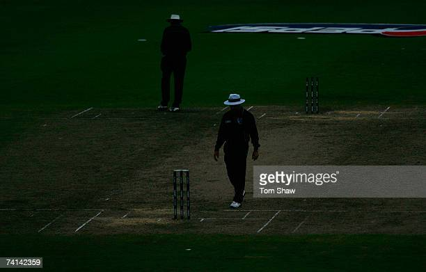 Umpires Aleem Dar and Steve Bucknor walk to their positions in the dark during the ICC Cricket World Cup Final between Australia and Sri Lanka at the...