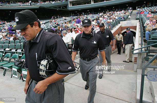Umpires Alfonso Marquez Tim Timmons and Chuck Meriwether walk onto the field before the Colorado Rockies game against the Arizona Diamondbacks at...