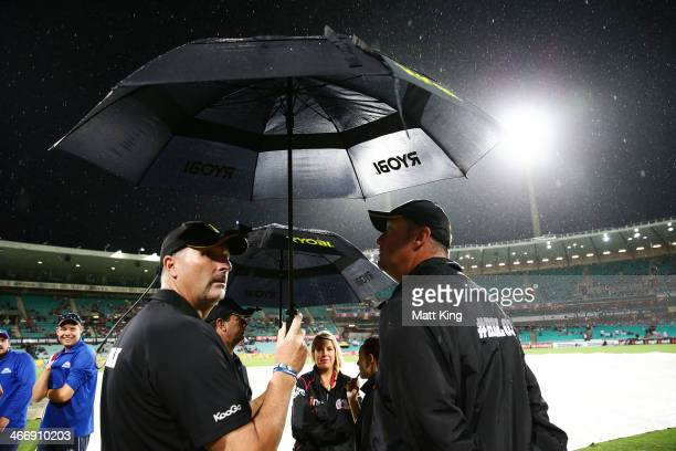 Umpires and ground staff assess conditions during an extended rain delay during the Big Bash League semi final match between the Sydney Sixers and...