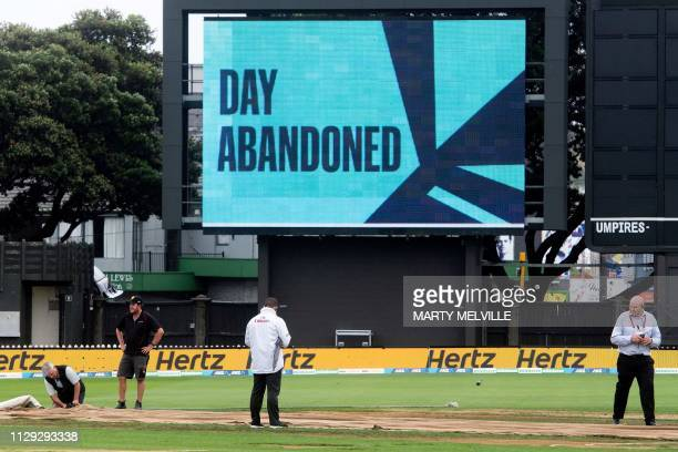 Umpires and officials stand out on the field as play is abandoned due to the weather on the second day during day two of the second Test cricket...