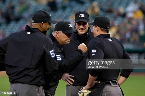 MLB umpires CB Bucknor Dale Scott John Tumpane and Quinn Wolcott stand on the field before the game between the Oakland Athletics and the Tampa Bay...